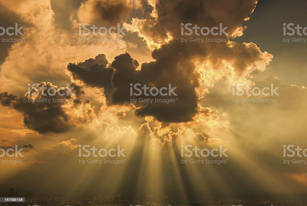 Rays of light shining through dark clouds for background stock photo