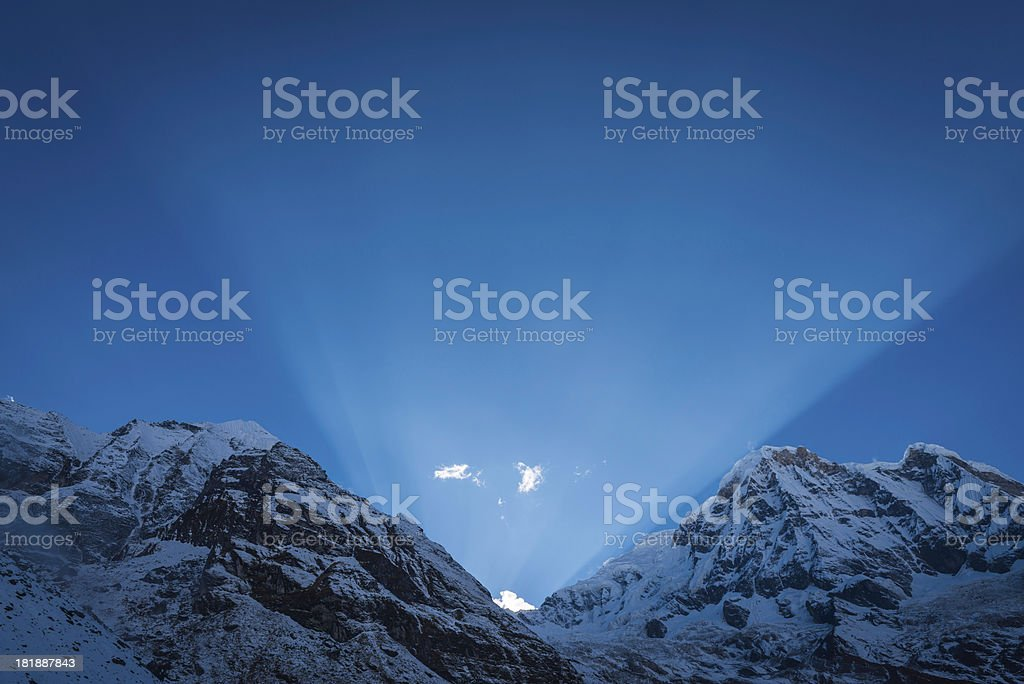 Rays of light shining through snowy mountain summits royalty-free stock photo