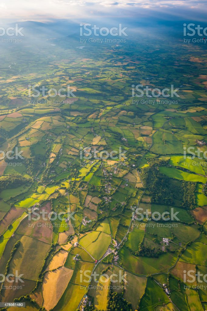 Rays of light through mountains onto green fields aerial photograph stock photo