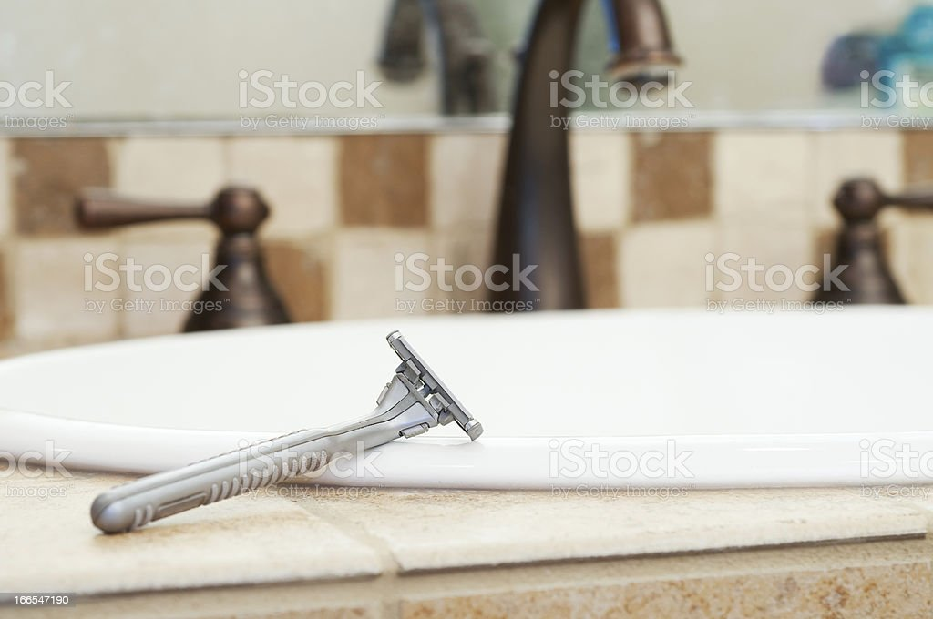 Razor Resting on Edge of Sink in Bathroom royalty-free stock photo