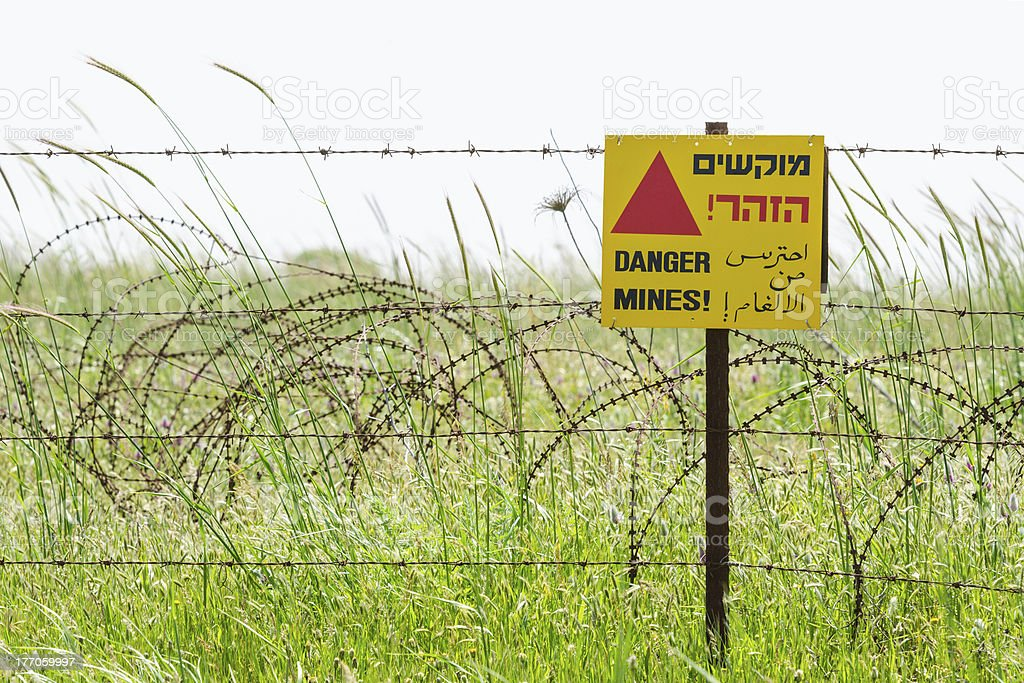 Razor wire guard fence and warning sign on mines field royalty-free stock photo