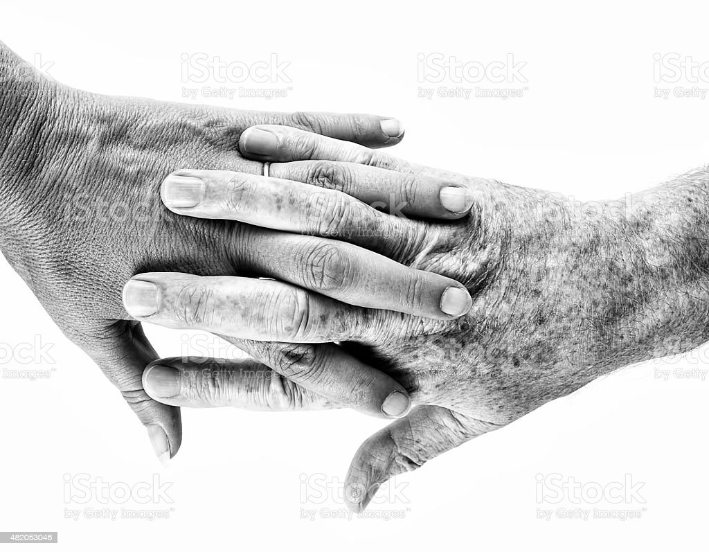 Reach out - mature man, woman holding hands on white. stock photo