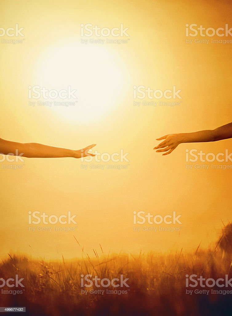 Reaching hands at sunset. stock photo