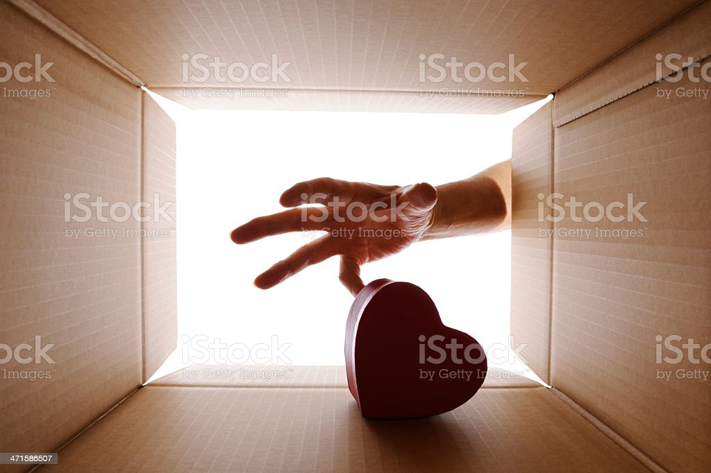 Reaching in cardboard box to pick up heart shape box royalty-free stock photo