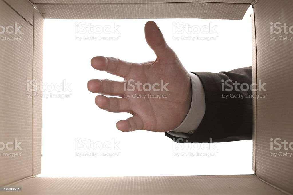 Reaching into a cardboard box stock photo