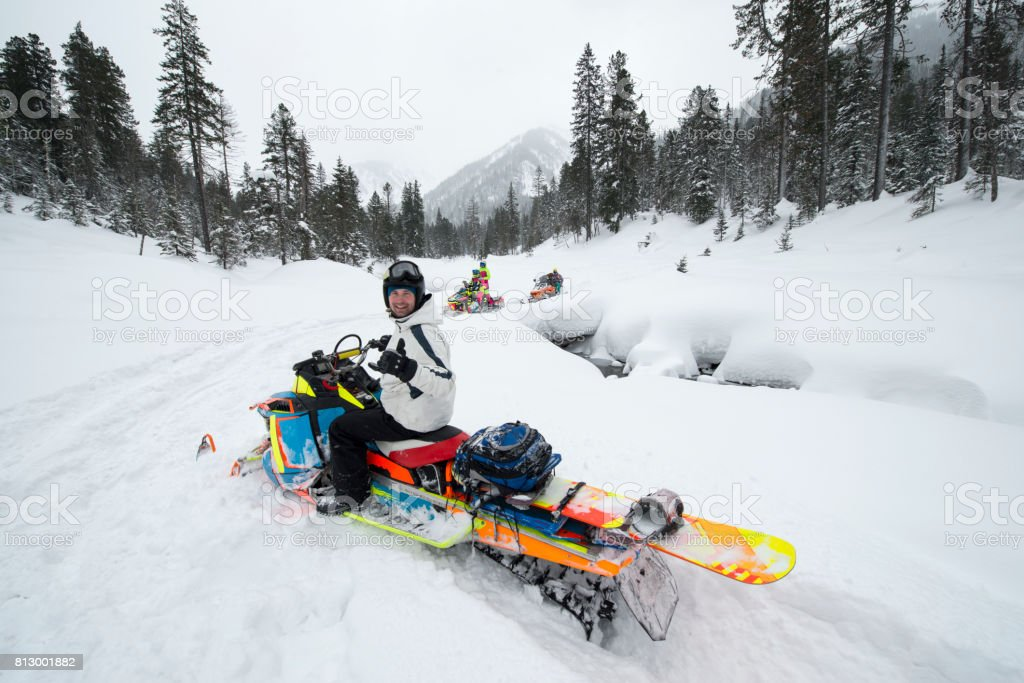 Reaching the snowboarding spots by snowmobile in mountain forest. stock photo
