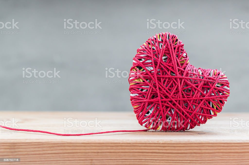 Read heart yarn on wood table over grunge cement background stock photo