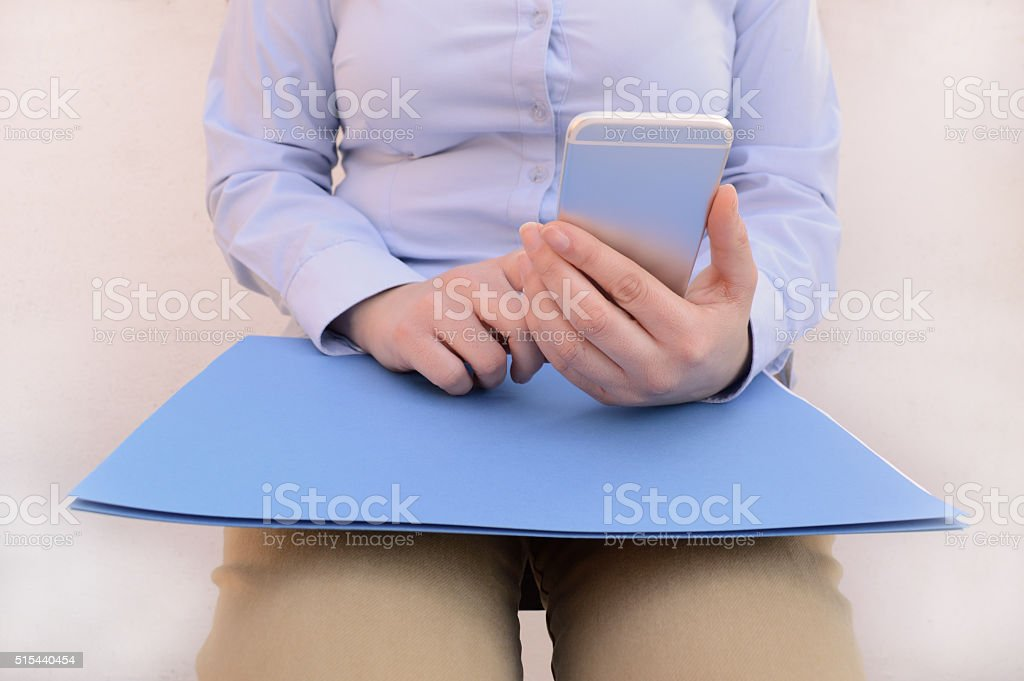 read phone at a waiting room stock photo