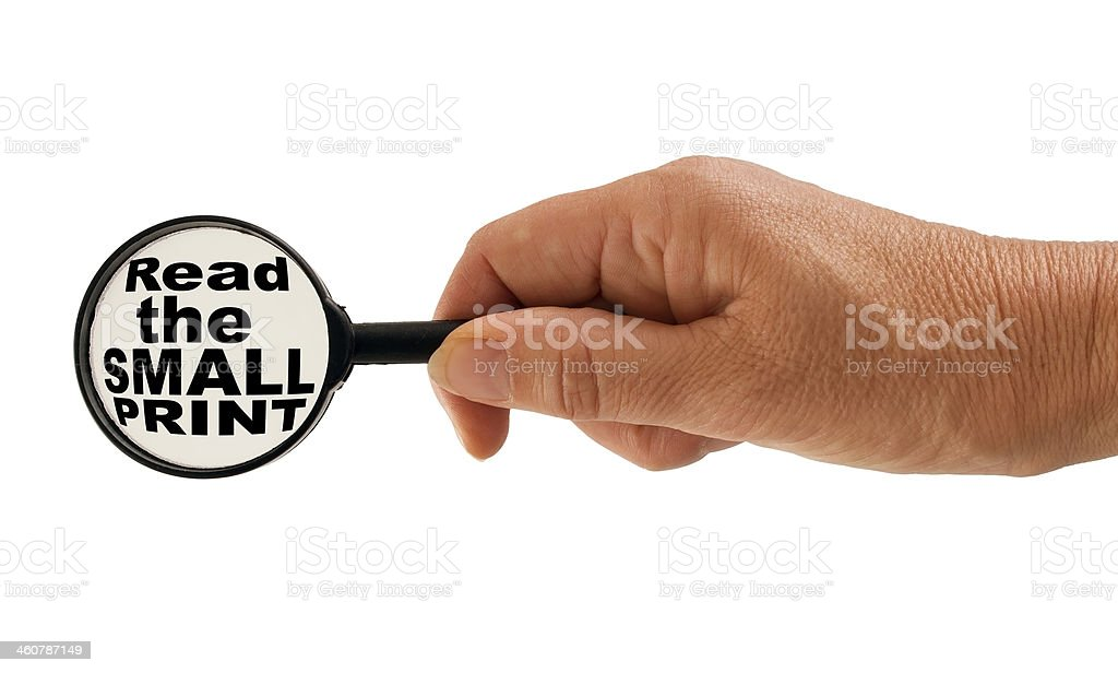 Read the small print warning - hand, magnifying glass message stock photo