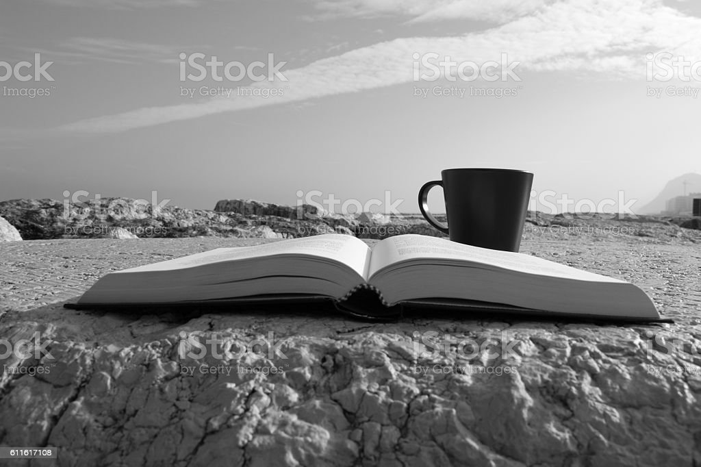 Reading a book and drinking a coffee stock photo