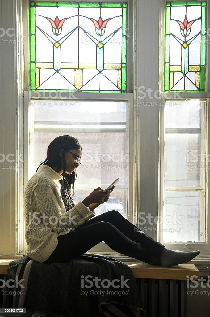 Reading a book sitting at the window stock photo