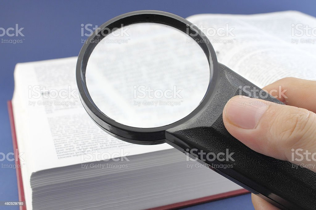Reading a book with magnifying glass stock photo