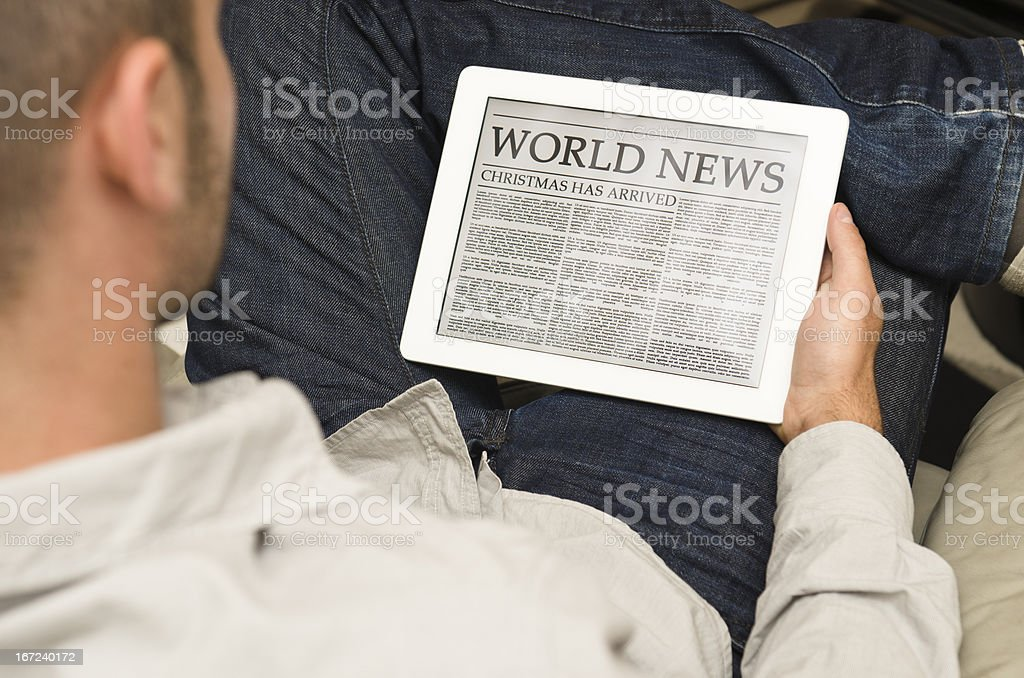 Reading a digital Christmas Newspaper on contemporary Tablet royalty-free stock photo