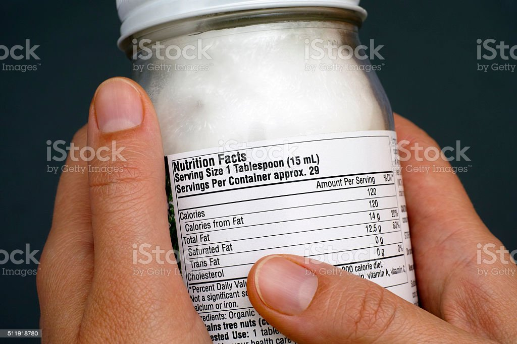 Reading a nutrition facts on coconut oil jar stock photo