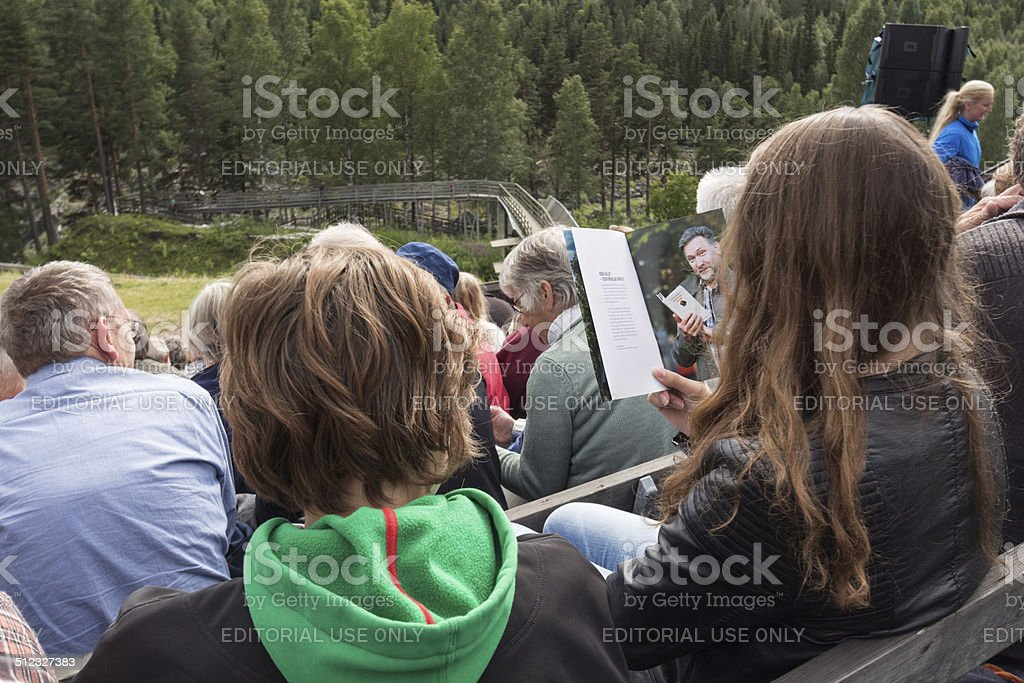 reading a pamphlet while waiting for the performance stock photo