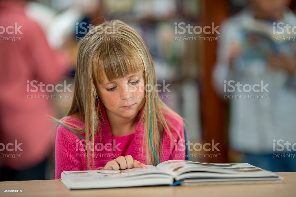 Reading a Picture Book in the Library stock photo