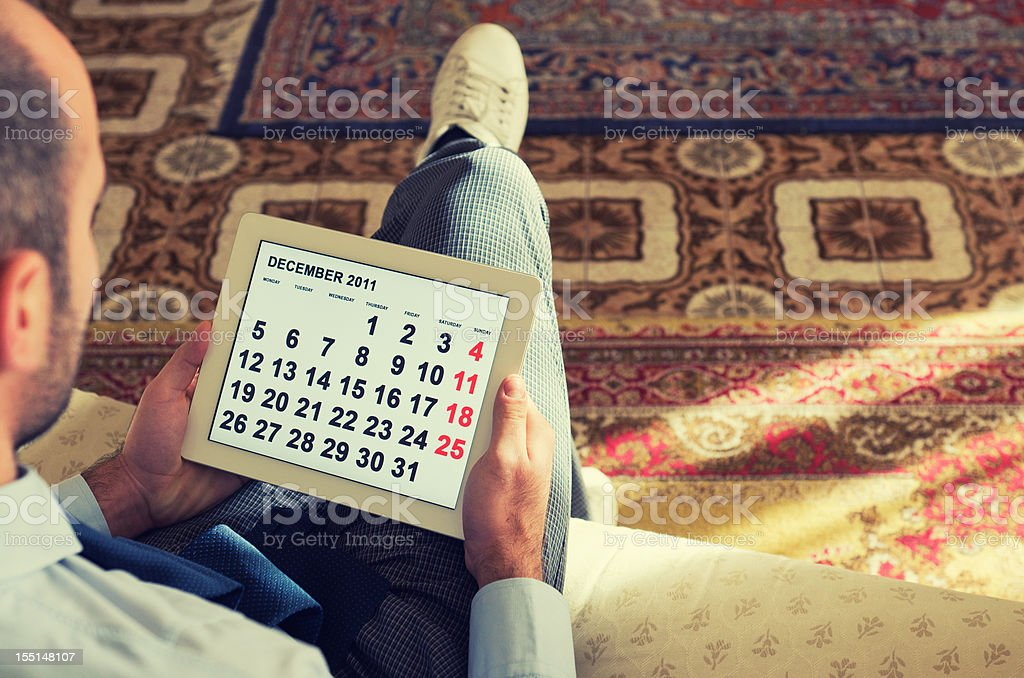 Reading agenda calendar on digital tablet stock photo