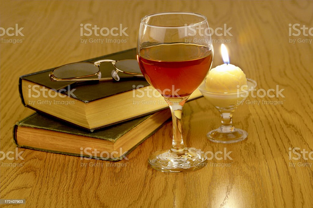 Reading and drinking by candlelight royalty-free stock photo