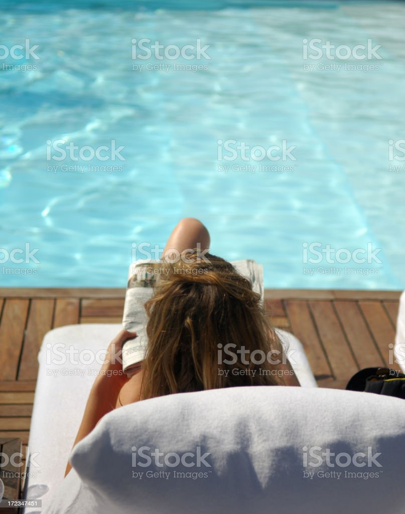 reading at the pool stock photo