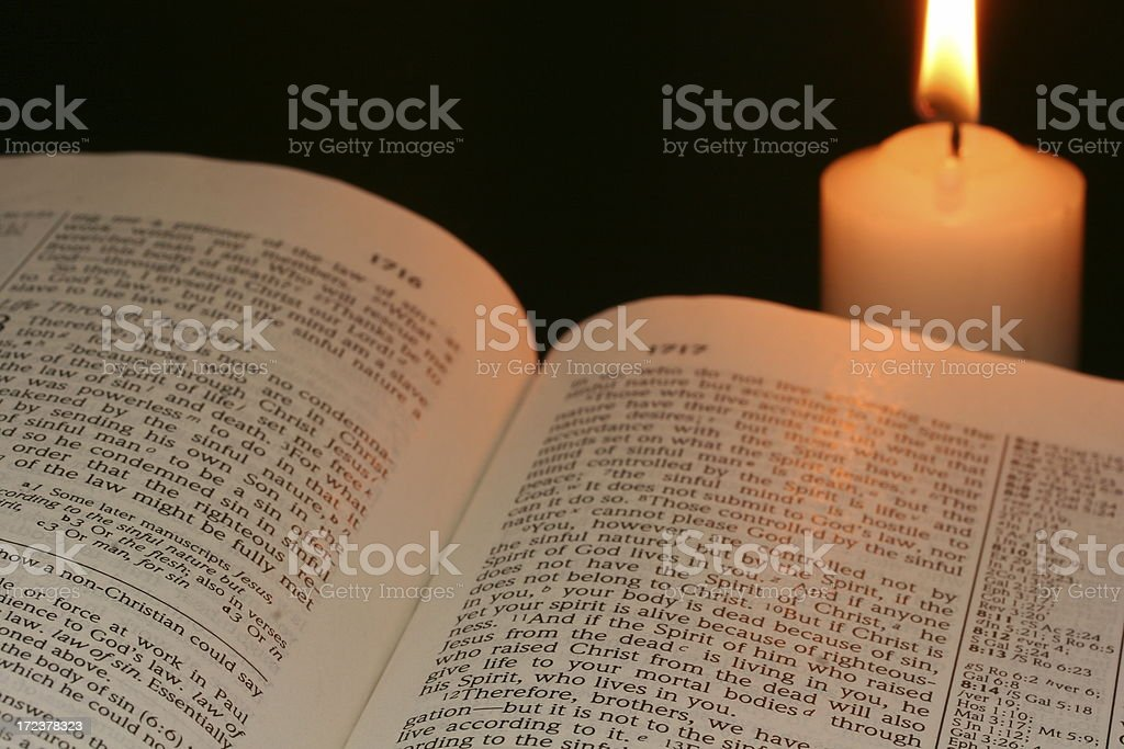Reading Bible in the dark with candle light royalty-free stock photo