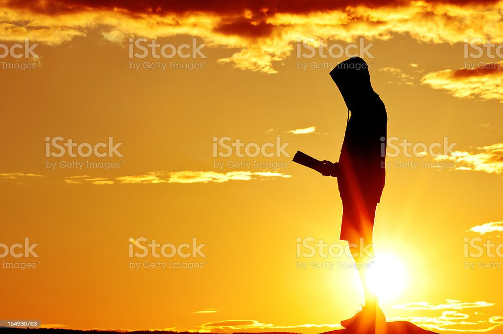 Reading Bible in the dramatic sunset - III royalty-free stock photo