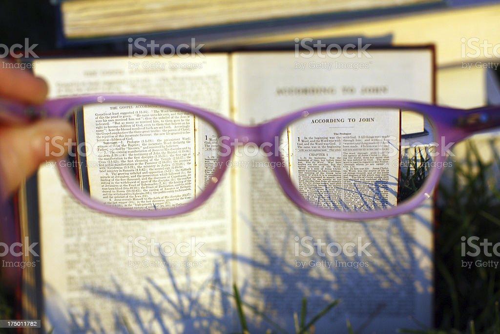 Reading Bible Through Glasses stock photo