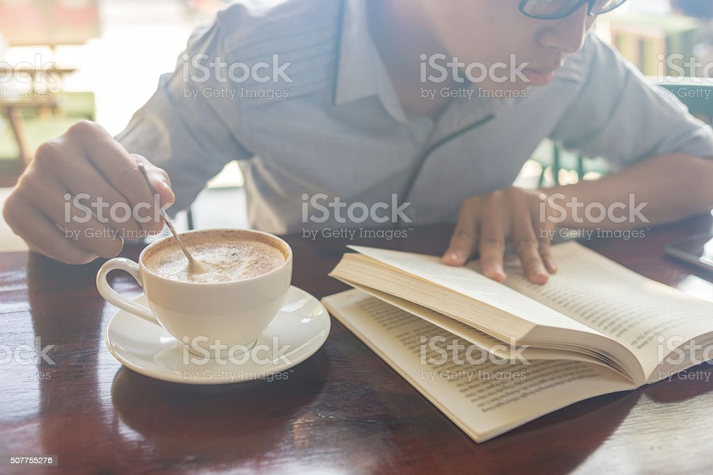 Reading book and stir coffee in the sunny day stock photo
