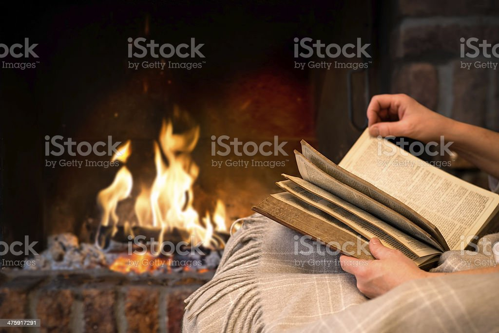 reading book by fireplace stock photo