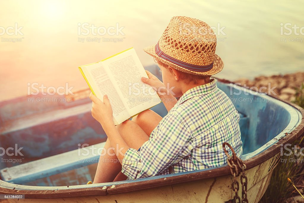 Reading boy in old boat stock photo