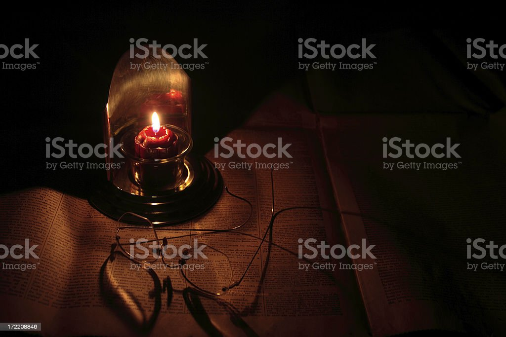 Reading by candlelight stock photo