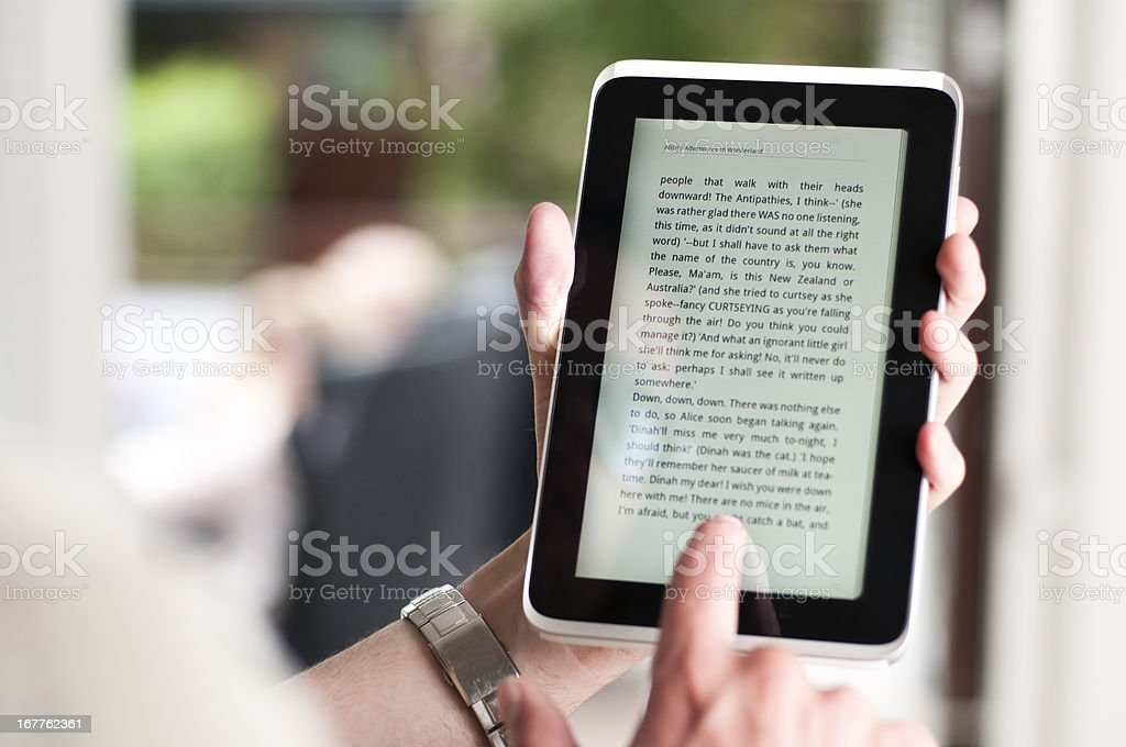 Reading eBook on a small digital tablet stock photo