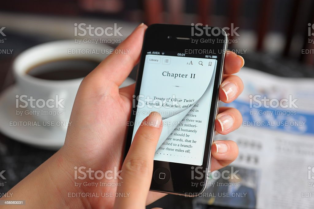 Reading e-book with iPhone 4 stock photo