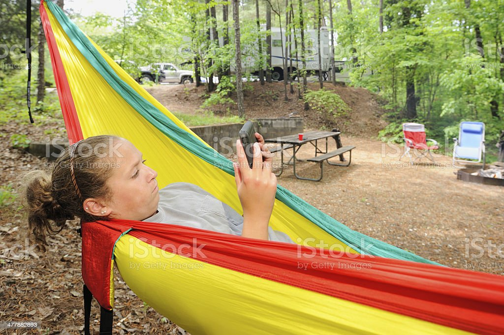 Reading electronic tablet in campground royalty-free stock photo