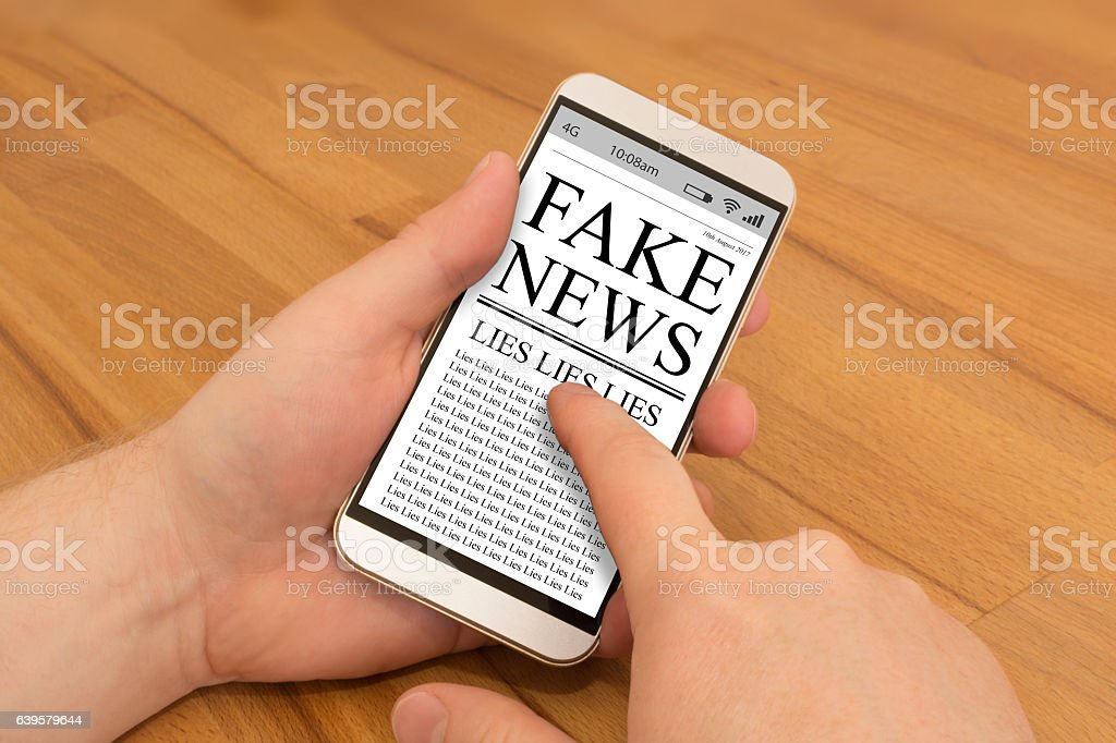 Reading Fake News on a Smartphone stock photo