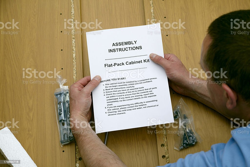 Reading flatpack kit instructions with flatback cabinet royalty-free stock photo