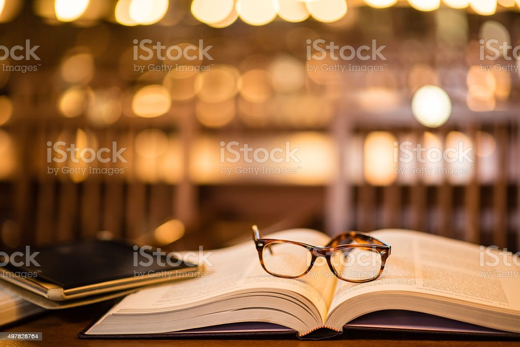 Reading glasses and digital tablet on book stock photo