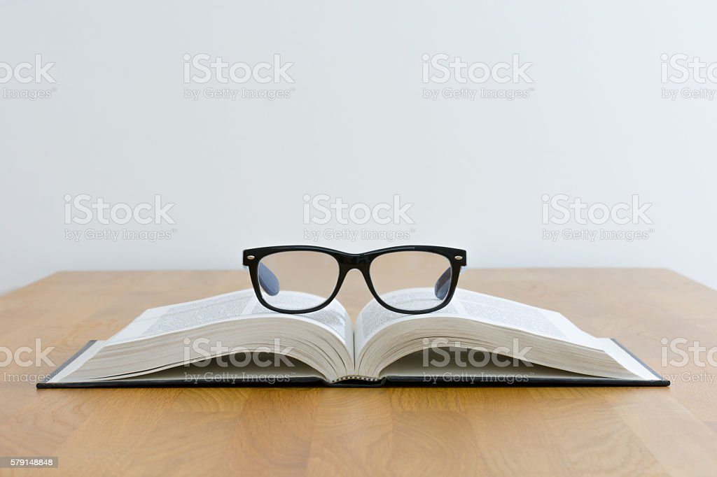 Reading glasses on top of book stock photo