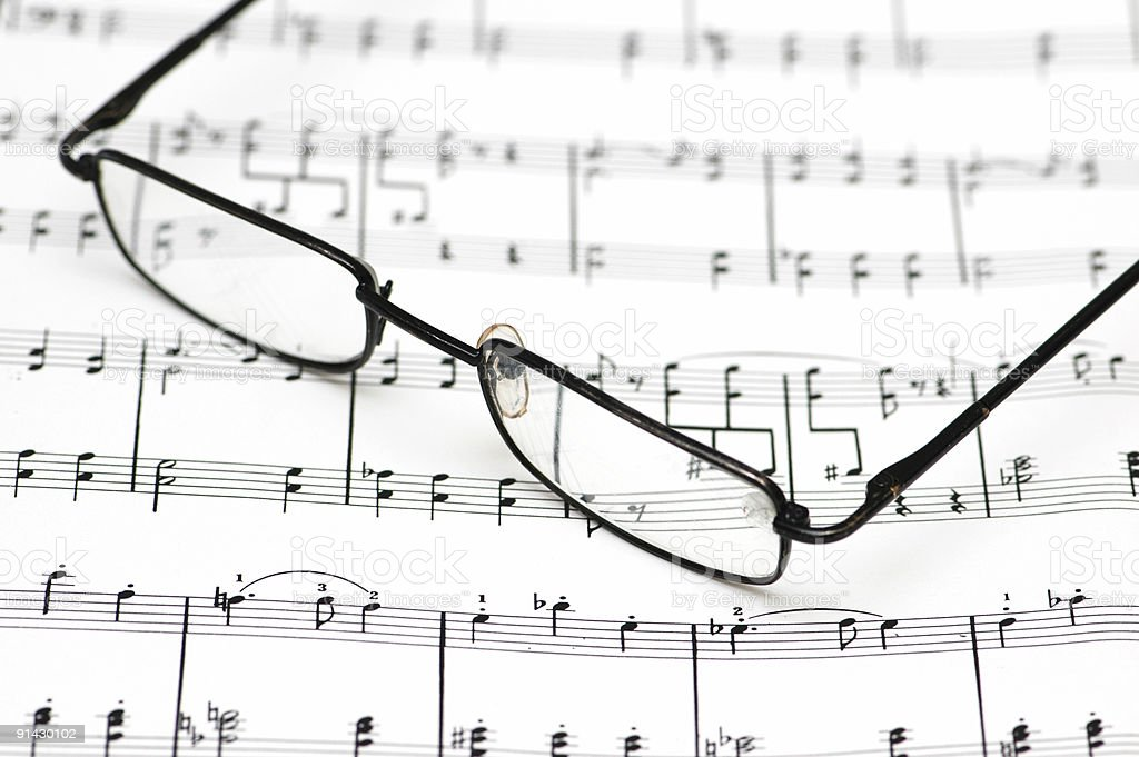 Reading glasses over the music sheets stock photo