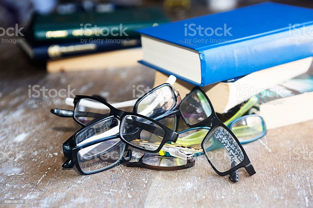 Reading glasses piled on a desk with books stock photo
