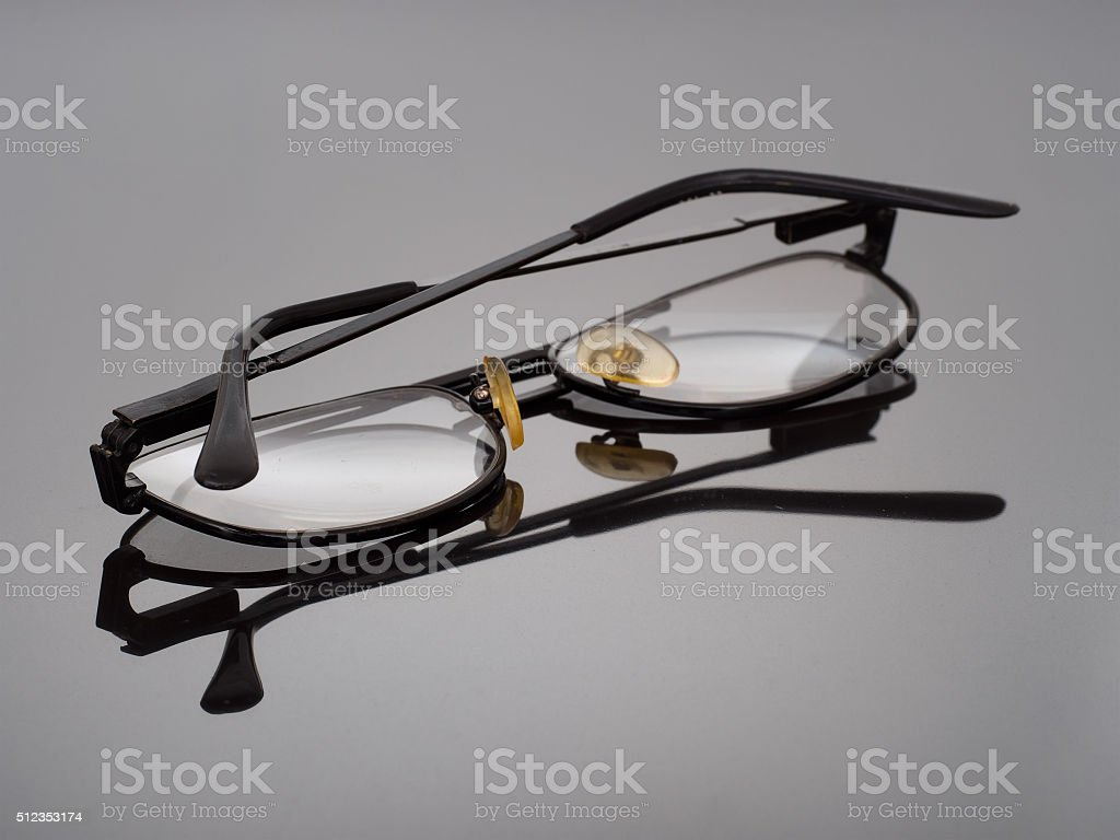 Reading glasses reflected on dark textured background stock photo