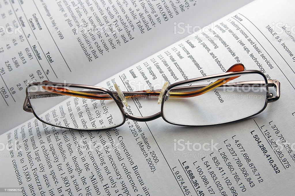 Reading glasses resting on textbook royalty-free stock photo