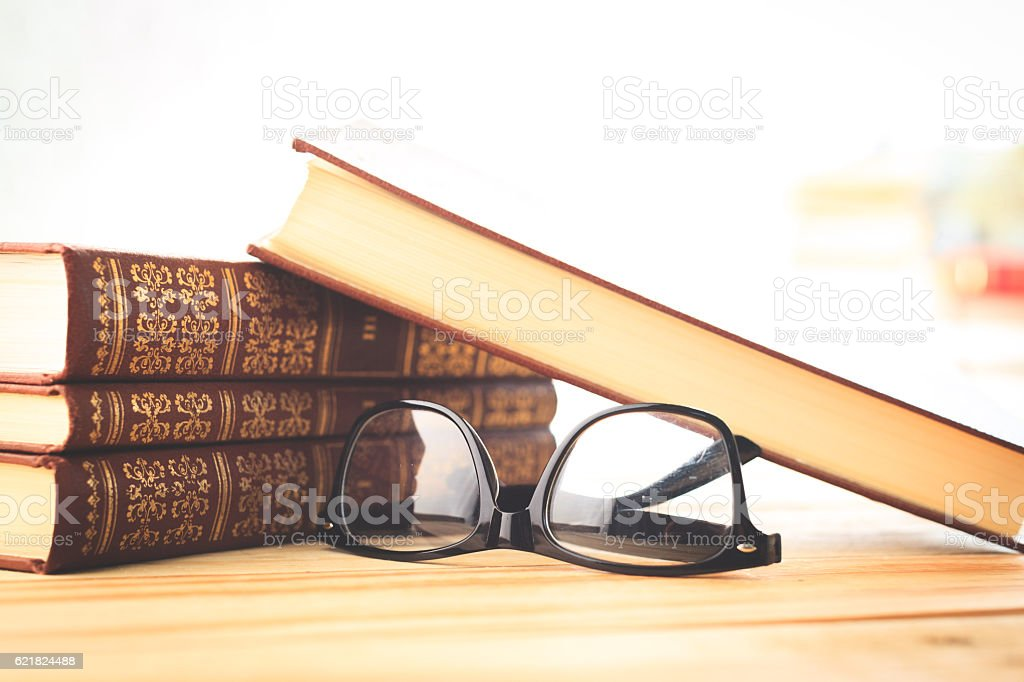 reading glasses with books on the table stock photo
