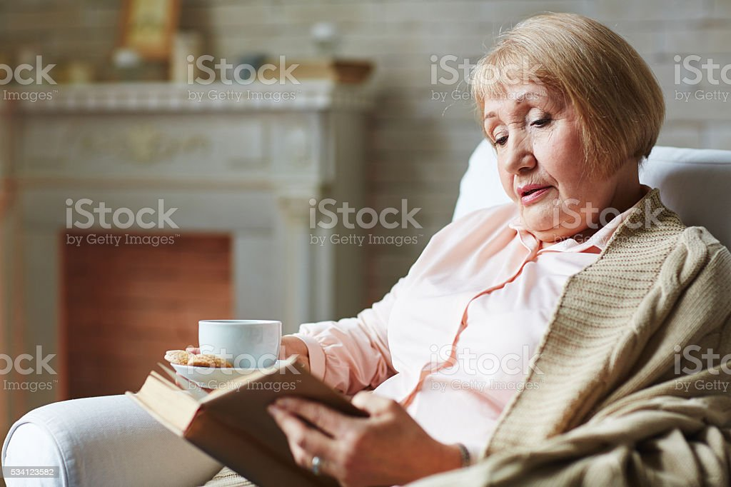 Reading in armchair stock photo
