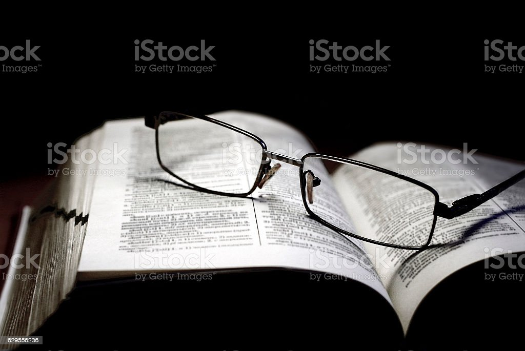 Reading, information and education concept - book and glasses stock photo