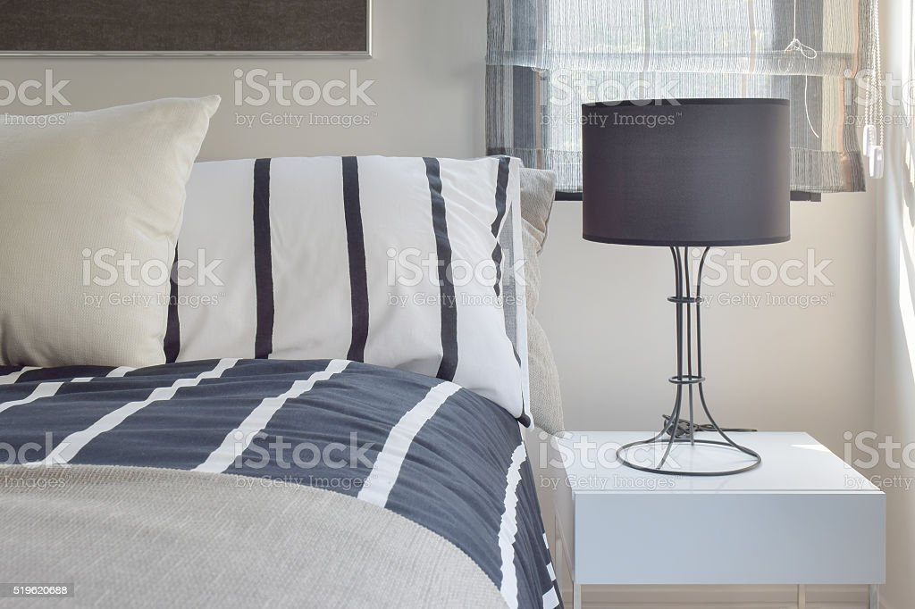 Reading lamp with black shade lamp on bedside table stock photo