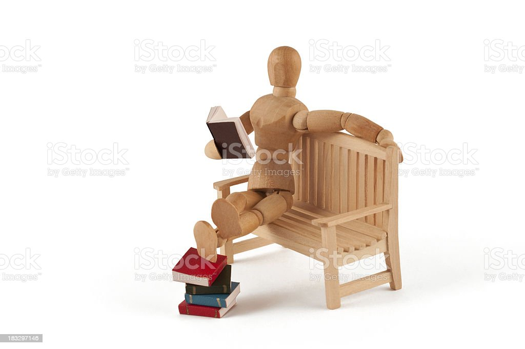 reading mannequin relaxing at a bench with feet on books stock photo
