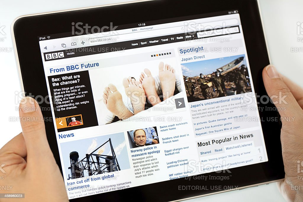 Reading news on  Apple iPad2 stock photo