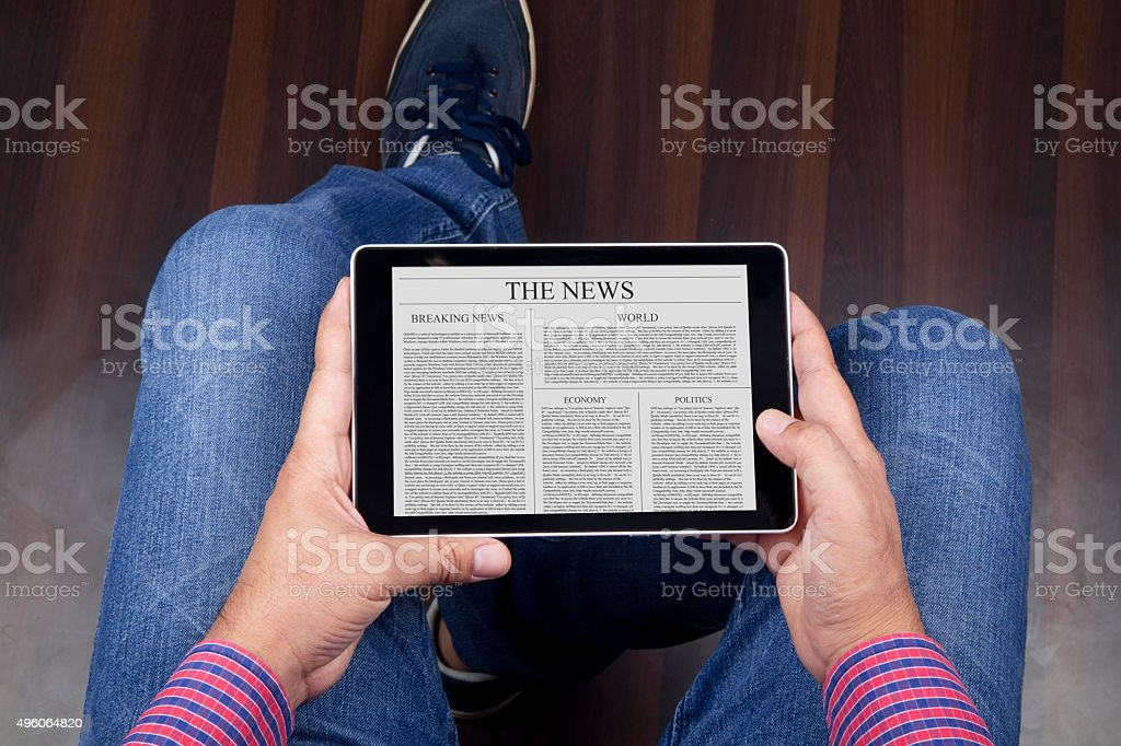 Reading news on digital tablet stock photo