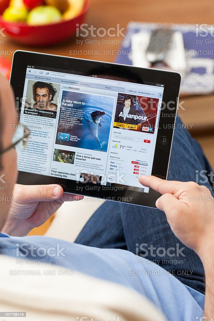 Reading news on ipad stock photo