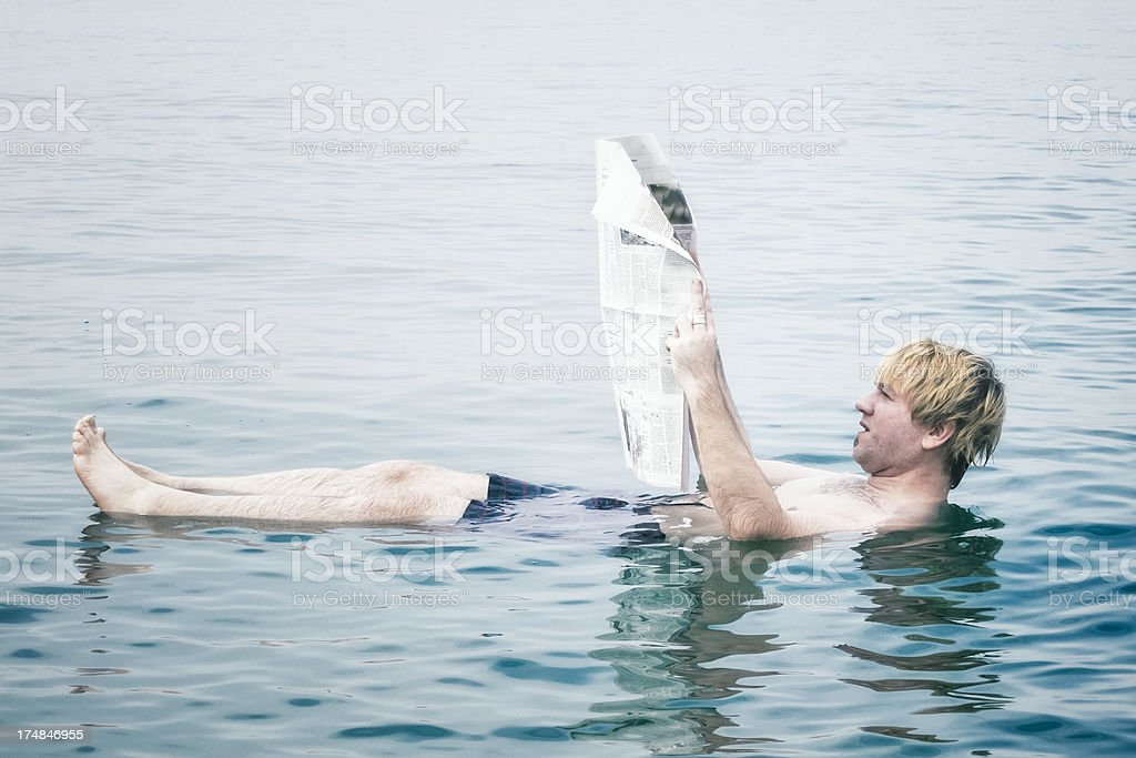 Reading newspaper in the Dead Sea royalty-free stock photo